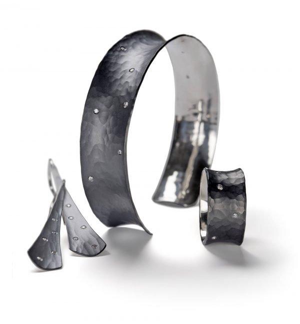 black bracelet, ring, and earrings