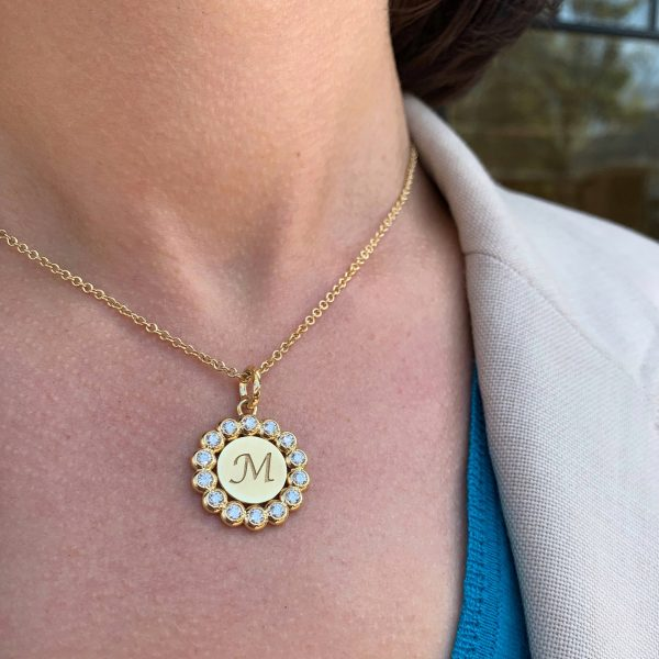 Gold and diamond pendant with an engraved M
